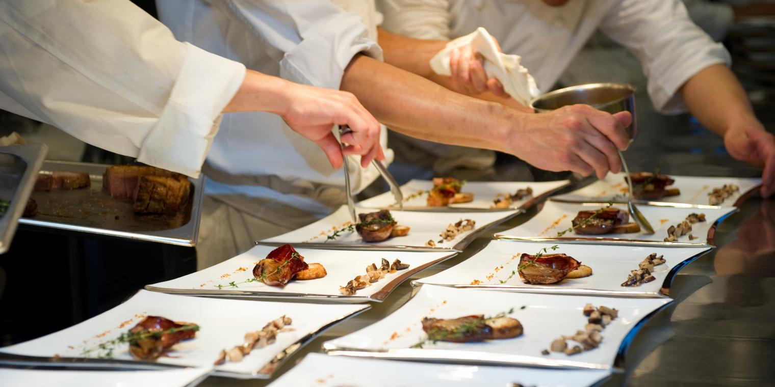 Chefs preparing food on a plate