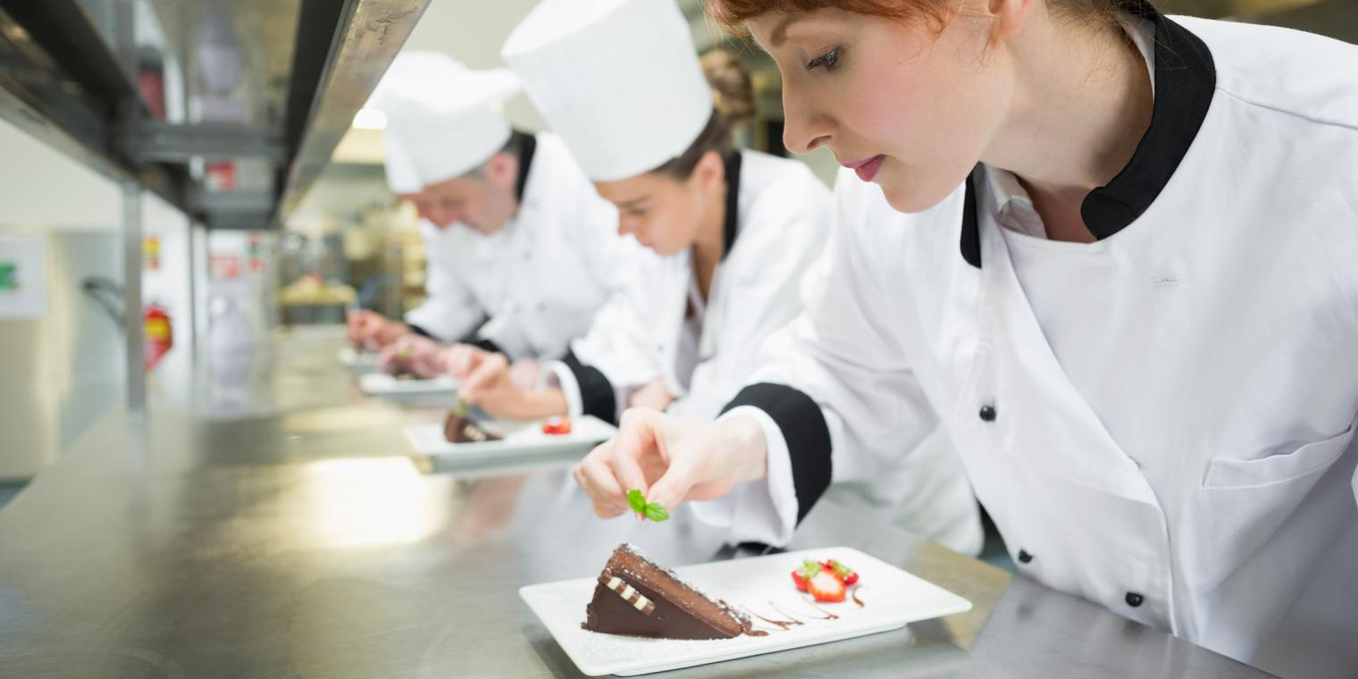 a group of chef preparing desert on a plate
